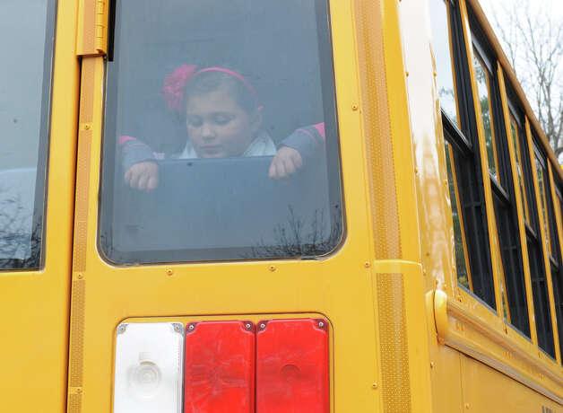 A girl looks out the window in the back of a bus as students are let out of school early at Elsmere Elementary School due to Hurricane Sandy on Monday, Oct. 29, 2012 in Delmar, N.Y. (Lori Van Buren / Times Union) Photo: Lori Van Buren