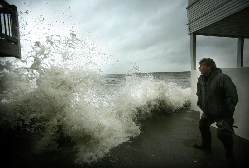 Jay Johnson of Milford watches as a wave from the onset of Hurricane Sandy crashes into a waterfront