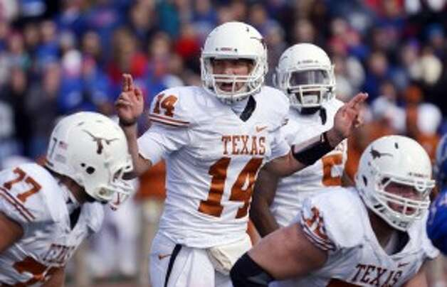 Texas quarterback David Ash (14) calls out instructions to his team during the first half of an NCAA college football game against Kansas in Lawrence, Kan., Saturday, Oct. 27, 2012. (AP Photo/Reed Hoffmann)