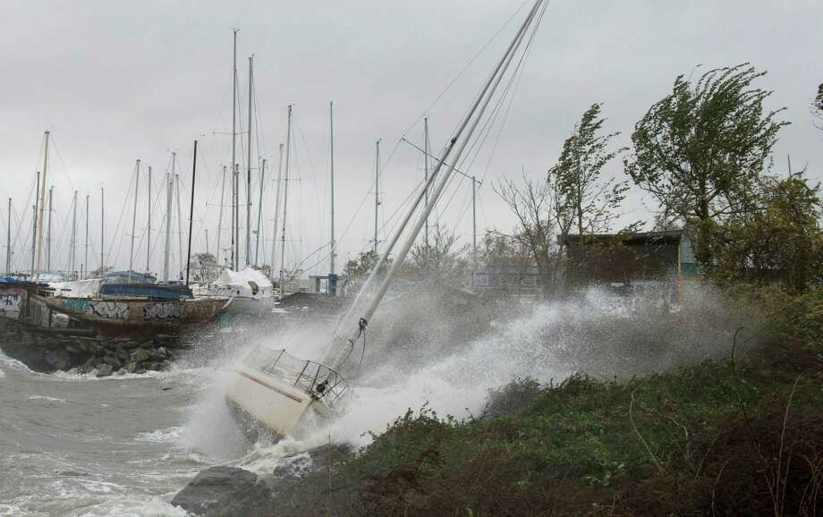 A sailboat smashes on the rocks after breaking free from its mooring on City Island October 29, 2012 in New York. Hurricane Sandy's winds picked up speed as the storm made a left turn toward the East Coast.  Photo: DON EMMERT, AFP/Getty Images / 2012 AFP