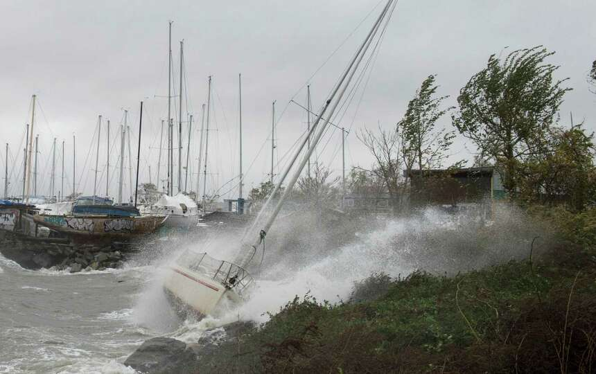 A sailboat smashes on the rocks after breaking free from its mooring on City Island October 29, 2012