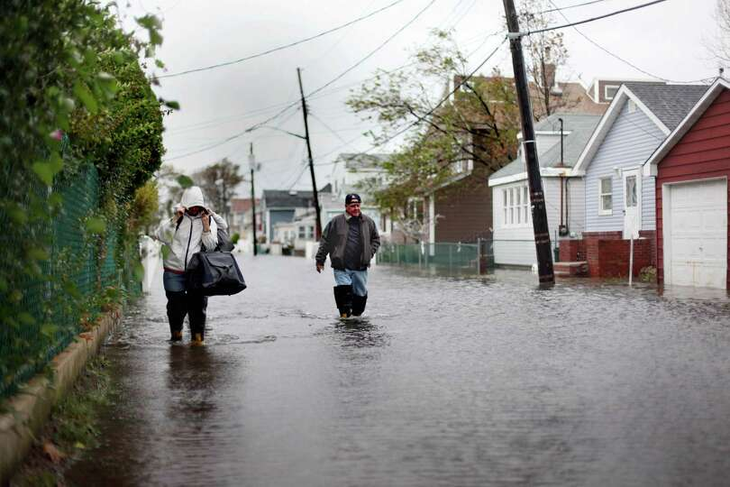 People wade through flood water in Broad Channel as Hurricane Sandy begins to affect the area on Oct
