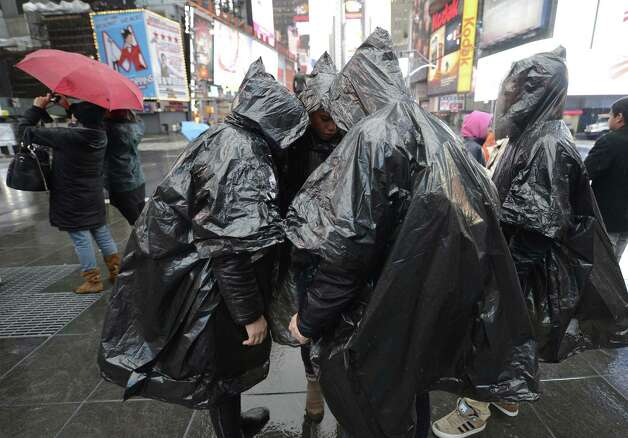 "Tourists in Times Square with platic panchos October 29, 2012 as New Yorkers prepare for Hurricane Sandy expected to hit the city later tonight. Much of the eastern United States was in lockdown mode October 29, 2012 awaiting the arrival of a hurricane dubbed ""Frankenstorm"" that threatened to wreak havoc on the area with storm surges, driving rain and devastating winds. Photo: TIMOTHY A. CLARY, AFP/Getty Images / 2012 AFP"