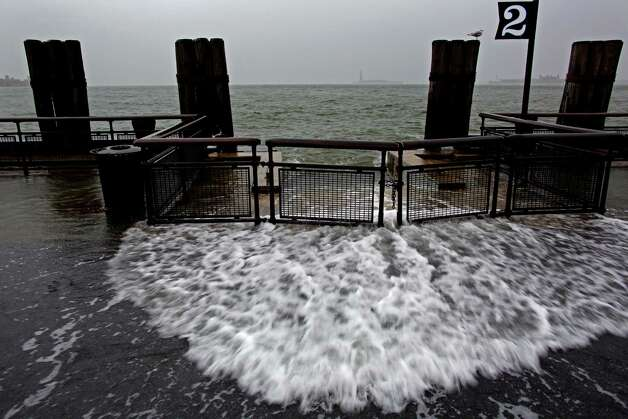 Waves wash over the sea wall near high tide at Battery Park in New York, Monday, Oct. 29, 2012 as Hurricane Sandy approaches the East Coast. Hurricane Sandy continued on its path Monday, forcing the shutdown of mass transit, schools and financial markets, sending coastal residents fleeing, and threatening a dangerous mix of high winds and soaking rain. (AP Photo/Craig Ruttle) Photo: Craig Ruttle, FRE / FR61802 AP