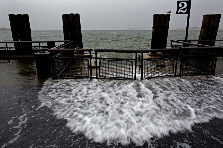 Waves wash over the sea wall near high tide at Battery Park in New York, Monday, Oct. 29, 2012 as Hurricane Sandy approaches the East Coast. Hurricane Sandy continued on its path Monday, forcing the shutdown of mass transit, schools and financial markets, sending coastal residents fleeing, and threatening a dangerous mix of high winds and soaking rain.(AP Photo/Craig Ruttle) Photo: Craig Ruttle, FRE / FR61802 AP