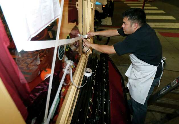 Oswaldo Falleres puts tape on the window of a restaurant in preparation for the arrival of superstorm Sandy, Sunday, Oct. 28, 2012, in Hoboken, N.J. Tens of thousands of people were ordered to evacuate coastal areas Sunday as big cities and small towns across the U.S. Northeast braced for the onslaught of a superstorm threatening some 60 million people along the most heavily populated corridor in the nation. (AP Photo/Julio Cortez) Photo: Julio Cortez, STF / AP