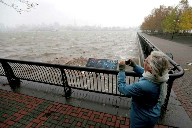 Sandy Martiny, of Jersey City, N.J., takes a photo of the wave activity on the Hudson River as the New York City skyline peeks through light rain on the waterfront as the Hurricane Sandy moves into the Northern New Jersey Region, Monday, Oct. 29, 2012, in Hoboken, N.J. Hurricane Sandy continued on its path Monday, as the storm forced the shutdown of mass transit, schools and financial markets, sending coastal residents fleeing, and threatening a dangerous mix of high winds and soaking rain.  (AP Photo/Julio Cortez) Photo: Julio Cortez, STF / AP