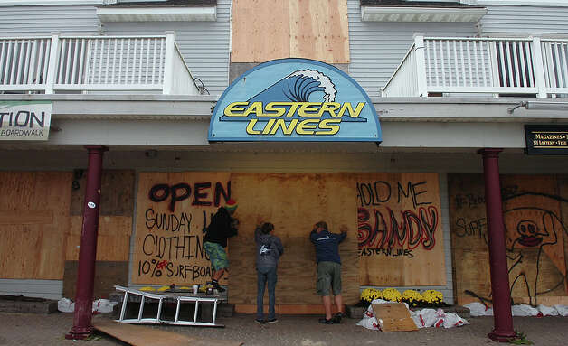 Business owners along Ocean Avenue in Belmar, N.J., board up windows and sandbag their properties on Sunday, Oct. 28, 2012, in preparation for Hurricane Sandy. (AP Photo/The Record of Bergen County, Kate Collins) ONLINE OUT; MAGS OUT; TV OUT; INTERNET OUT;  NO ARCHIVING; MANDATORY CREDIT Photo: Kate Collins, MBR / The Record of Bergen County
