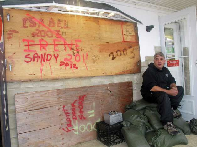 "Mark Palazzolo, owner of a bait and tackle shop on the Manasquan Inlet in Point Pleasant Beach, N.J., sits next to wood he has used to board up his business in previous major storms, Sunday, Oct. 28, 2012, in Point Pleasant Beach, N.J. Of Hurricane Sandy, he said, ""I think this is going to do us in."" (AP Photo/Wayne Parry) Photo: Wayne Parry, STF / AP"