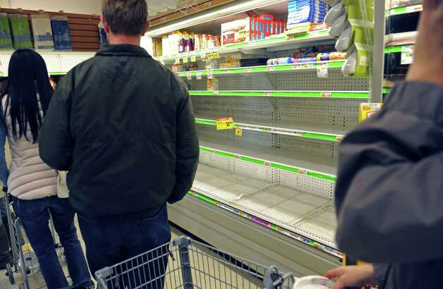 Shoppers pass an empty egg section of a Food Emporium supermarket in the West Village in the wake of the storm, Sunday, Oct. 28, 2012, in New York. Tens of thousands of people were ordered to evacuate coastal areas Sunday as big cities and small towns across the U.S. Northeast braced for the onslaught of a superstorm threatening some 60 million people along the most heavily populated corridor in the nation. (AP Photo/ Louis Lanzano) Photo: Louis Lanzano, FRE / FR77522 AP