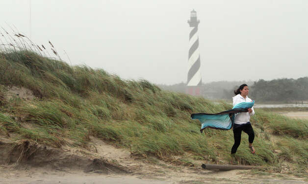 Teresa Perez of Buxton, N.C., runs off a sand dune near Cape Hatteras Lighthouse on Hatteras Island Sunday, Oct. 28, 2012, as Hurricane Sandy works its way north, battering the U.S. East Coast. (AP Photo/The Virginian-Pilot, Steve Earley) Photo: Steve Earley, MBI / The Virginian-Pilot