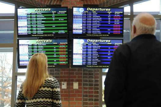 Colleen Holloway, left, and her father Tom Steigerwald, right, examine the flight board at Albany International Airport, Monday morning, Oct. 29, 2012. Holloway was lucky enough to make her flight back to Fort Lauderdale, Fla. Many flights in the northeast were canceled because of Hurricane Sandy. (Will Waldron / Times Union) Photo: Ww