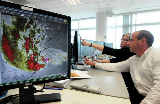 National Weather Service meteorologists Vasil Koleci, left, and Ingrid Amberger, right, monitor Hurricane Sandy Monday,  Oct. 30, 2012, at the national weather facility  in Albany, N.Y. (Will Waldron / Times Union) Photo: Ww
