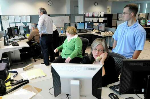 National Weather Service meteorologist Ingrid Amberger, center, on phone, monitors Hurricane Sandy with her colleagues Monday, Oct. 30, 2012, at the weather service facility  in Albany, N.Y. (Will Waldron / Times Union) Photo: Ww