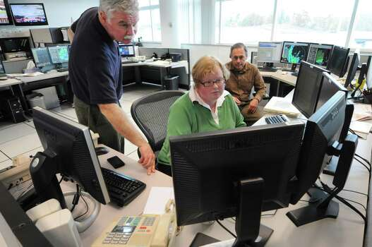 Ray O?Keefe, left, chief meteorologist at the National Weather Service facility  in Albany, N.Y., works with Britt Westergard, center, and George Maglaras,  right, as they discuss Hurricane Sandy tidal surge predictions for the Hudson River, Monday, Oct. 30, 2012. (Will Waldron / Times Union) Photo: Ww