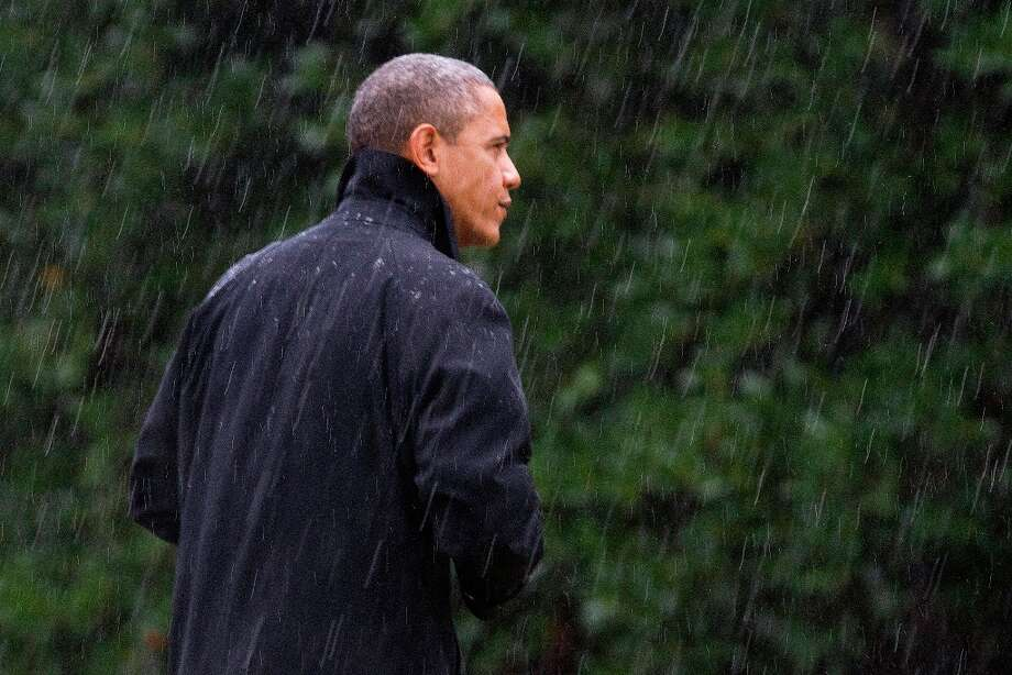 President Barack Obama walks into the White House in a driving rain hours before Hurricane Sandy decimated the Jersey Shore.  An aloof president has the chance to mobilize, lead and become the Comforter in Chief.. Photo: Jacquelyn Martin, Associated Press / AP