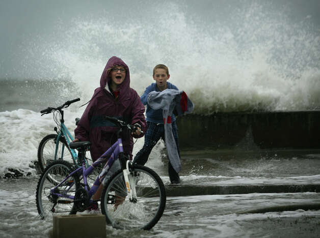 Siblings Megan, 11, and Brian Flanagan, 12, of Milford, react as a large wave from Hurricane Sandy crashes over the seawall on Point Beach Drive in Milford on Monday, October 29, 2012. Photo: Brian A. Pounds