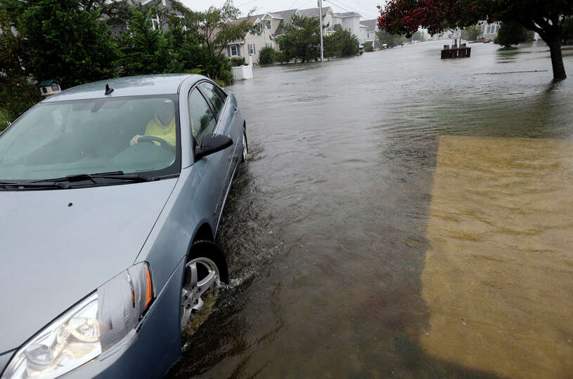Richard Thomas moves a neighbors' car out of the rising water as Hurricane Sandy bears down on the E