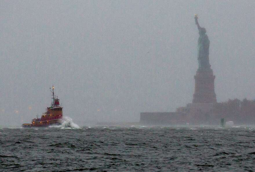 Waves crash over the bow of a tug boat as it passes near the Statue of Liberty in New York  Monday,