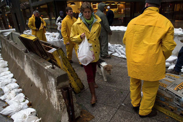 A pedestrian walks her dog through a working crew as they stack sandbags beside concrete barriers to protect buildings near the World Financial Center in anticipation of massive flooding, Monday, Oct. 29, 2012, in New York. Hurricane Sandy bore down on the Eastern Seaboard's largest cities Monday, forcing the shutdown of mass transit, schools and financial markets, sending coastal residents fleeing, and threatening a dangerous mix of high winds, soaking rain and a seawater surge of anywhere from 6 to 11 feet. Photo: AP