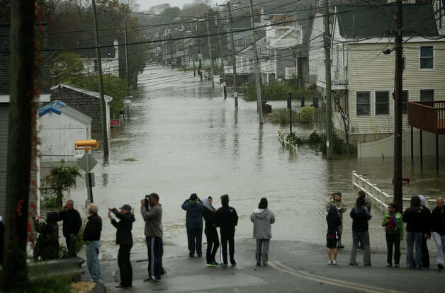 Residents survey the scene of a flooded Melba Street in the Bayview section of Milford on Monday, October 29, 2012. Photo: Brian A. Pounds