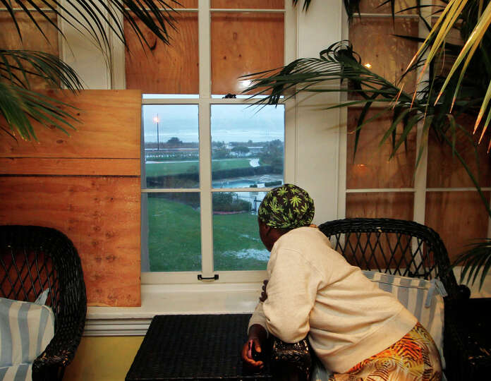 Judiann Parker watches the rough surf of the Atlantic Ocean from a partially boarded-up window early