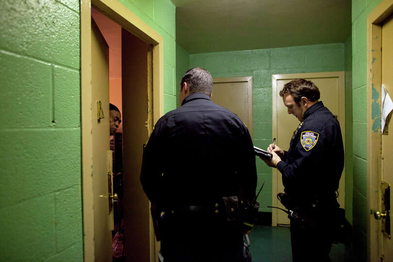 New York City police officers go door to door in a housing project to take note of which residents a
