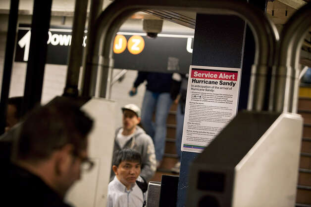 A sign announcing the temporary closure of the New York subway system, due to Hurricane Sandy, is seen in the subway prior to the arrival of Hurricane Sandy on October 28, 2012 in New York City. New York plans on shutting down the entire public transmit system starting at 7PM, Sunday night. Sandy, which has already claimed over 50 lives in the Caribbean, is predicted to bring heavy winds and floodwaters as the mid-atlantic region prepares for the damage. Photo: Andrew Burton, Getty Images / 2012 Getty Images