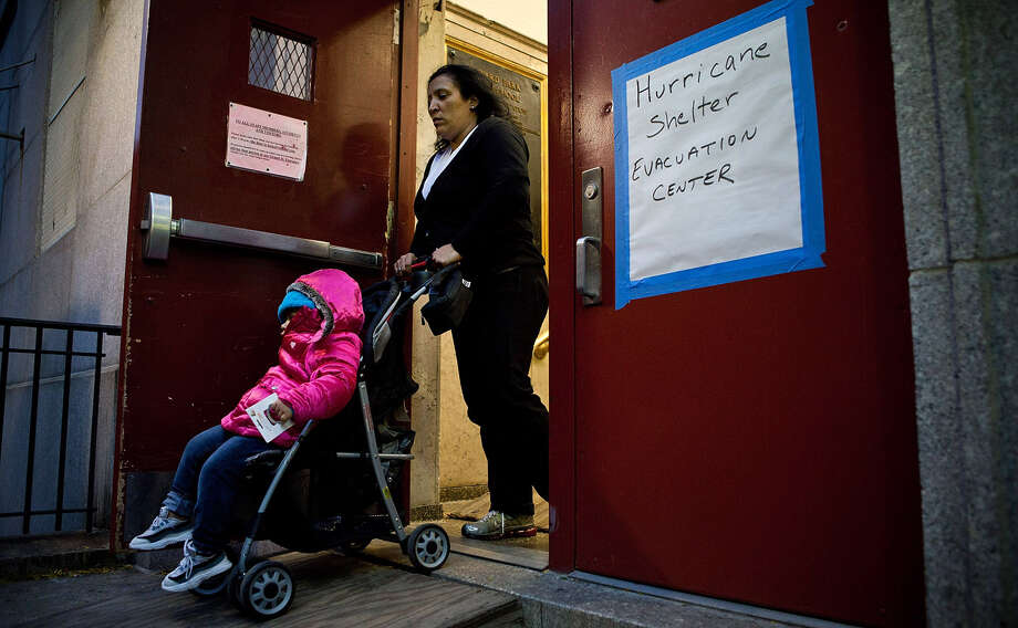 A woman and child leave Seward Park High School, which is doubling as an evacuation center for Hurricane Sandy, on October 28, 2012 in New York City. Sandy, which has already claimed over 50 lives in the Caribbean, is predicted to bring heavy winds and floodwaters as the mid-atlantic region prepares for the damage. Photo: Andrew Burton, Getty Images / 2012 Getty Images