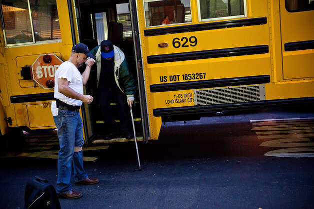 A man is helped off a bus while arriving at Seward Park High School, which is doubling as an  evacuation center for Hurricane Sandy, on October 28, 2012 in New York City. Sandy, which has already claimed over 50 lives in the Caribbean, is predicted to bring heavy winds and floodwaters as the mid-atlantic region prepares for the damage. Photo: Andrew Burton, Getty Images / 2012 Getty Images