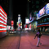 A lone pedestrian walks through an empty Times Square early, Monday, Oct. 29, 2012, in New York. Hurricane Sandy continued on its path Monday, forcing the shutdown of mass transit, schools and financial markets, sending coastal residents fleeing, and threatening a dangerous mix of high winds and soaking rain.