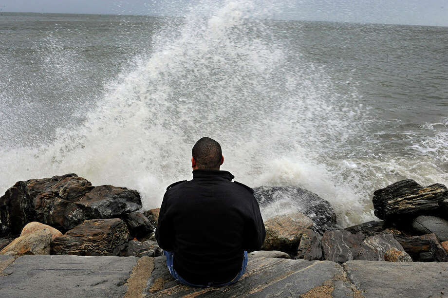Lamar Chambers watches waves as winds from hurricane Sandy reach Seaside Park in Bridgeport, Conn., Monday, Oct. 29, 2012. Hurricane Sandy continued on its path Monday, forcing the shutdown of mass transit, schools and financial markets, sending coastal residents fleeing, and threatening a dangerous mix of high winds and soaking rain. Photo: Jessica Hill, AP / FR125654 AP