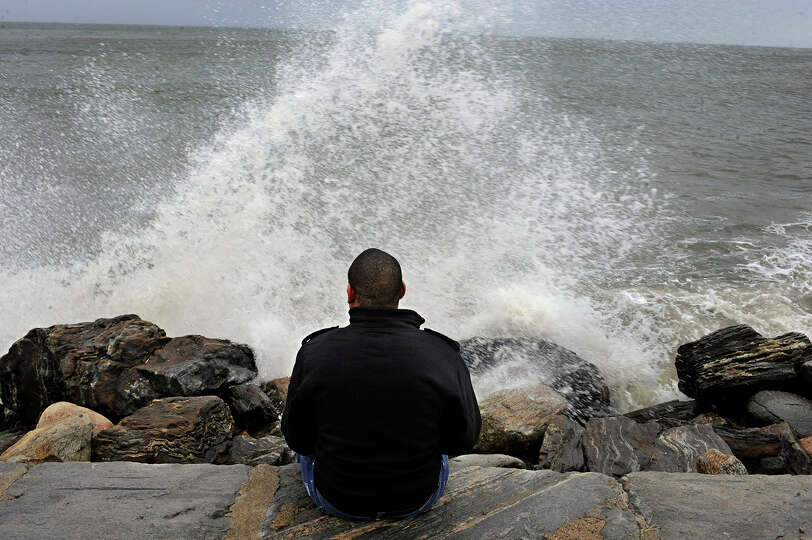 Lamar Chambers watches waves as winds from hurricane Sandy reach Seaside Park in Bridgeport, Conn