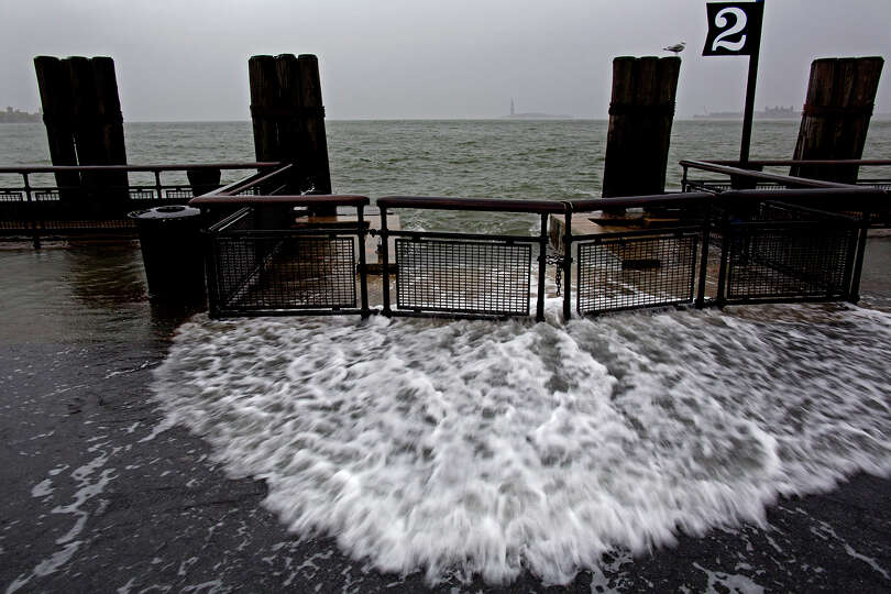 Waves wash over the sea wall near high tide at Battery Park in New York, Monday, Oct. 29, 2012 as Hu