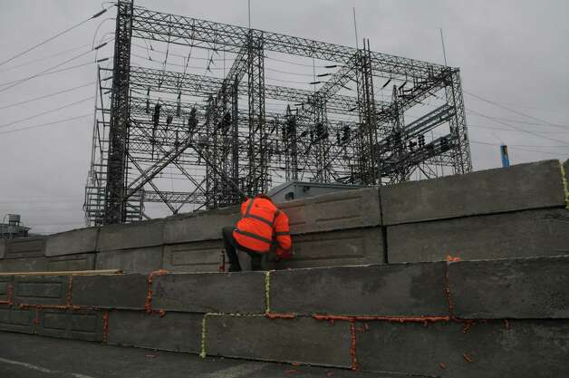 Crews from Connecticut Light and Power, O&G Industries and Marino Crane work on building a concrete wall to keep the CL&P South End Substation on Manhattan Street from flooding as Hurricane Sandy moves into Stamford, Conn., Oct. 29, 2012. The wall consists of two lines of 4,000 pound blocks stacked six feet high. The crew then shot foam into the cracks between the blocks and covered them with plastic. The substation powers most of the Stamford Downtown area. Photo: Keelin Daly / Stamford Advocate Riverbend Stamford, CT