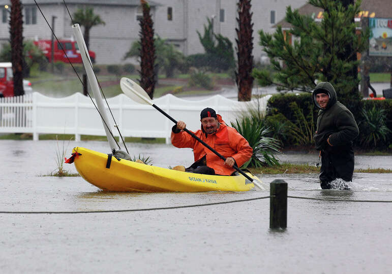 Allen Boyer paddles a kayak in floodwaters caused by Hurricane Sandy as Bobby Carnutte wades through