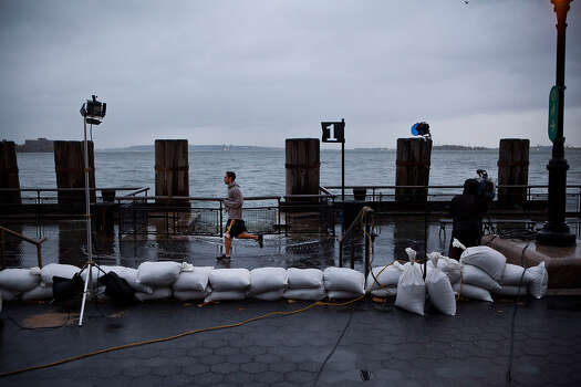 A man runs through a news broadcaster's shot in Battery Park during the arrival of Hurricane Sandy on October 29, 2012 in New York City. The core of Sandy's force is supposed to hit the New York area Monday night. Photo: Andrew Burton, Getty Images / 2012 Getty Images