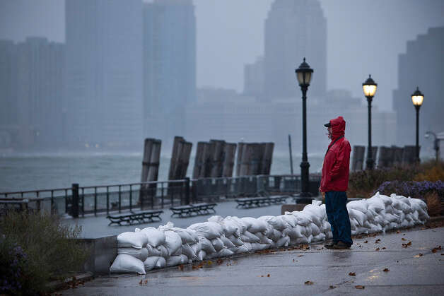 A man watches the waves in New York Harbor from Battery Park during the arrival of Hurricane Sandy on October 29, 2012 in New York City. The core of Sandy's force is supposed to hit the New York area Monday night. Photo: Andrew Burton, Getty Images / 2012 Getty Images