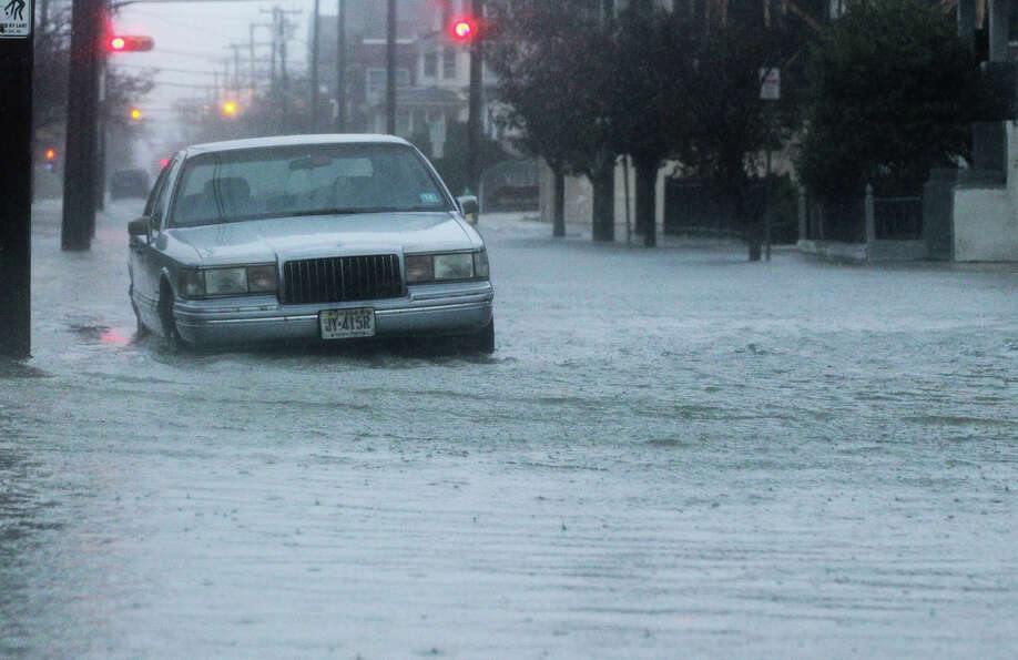 A car sits in a flooded street near the ocean ahead of Hurricane Sandy on October 29, 2012 in Atlant
