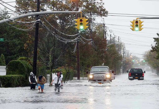 People make their way up a flooded Guy Lomardo Avenue as high tide and winds from Hurricane Sandy combine to flood the area on October 29, 2012 in Freeport, New York. The storm, which threatens 50 million people in the eastern third of the U.S., is expected to bring days of rain, high winds and possibly heavy snow. Photo: Bruce Bennett, Getty Images / 2012 Getty Images