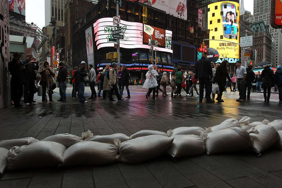 People walk by sand bags in front of a building in Times Square as Hurricane Sandy begins to affect the area on October 29, 2012 in New York City.  The storm, which threatens 50 million people in the eastern third of the U.S., is expected to bring days of rain, high winds and possibly heavy snow. New York Governor Andrew Cuomo announced the closure of all New York City will  bus, subway and commuter rail service as of Sunday evening. Photo: Spencer Platt, Getty Images / 2012 Getty Images