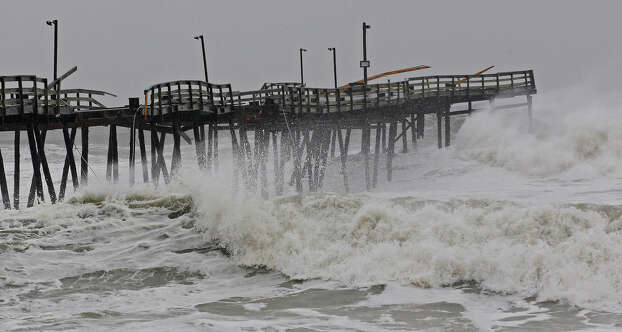 Waves from Hurricane Sandy crash onto the damaged Avalon Pier in Kill Devil Hills, N.C., Monday, Oct. 29, 2012 as Sandy churns up the east coast. Hurricane Sandy continued on its path Monday, as the storm forced the shutdown of mass transit, schools and financial markets, sending coastal residents fleeing, and threatening a dangerous mix of high winds and soaking rain.  Photo: Gerry Broome, AP / AP2012