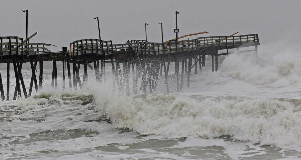 Waves from Hurricane Sandy crash onto the damaged Avalon Pier in Kill Devil Hills, N.C., Monday, Oct