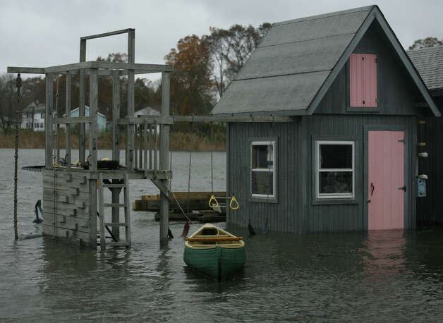 A canoe floats tied to a submerged children's swingset during flooding from Hurricane Sandy on Melba Street in the Bayview section of Milford on Monday, October 29, 2012. Photo: Brian A. Pounds