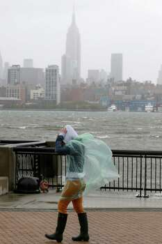 Heather Maschi, 24, tries to keep her hood on as gusty winds blow near the Hudson River, Monday, Oct. 29, 2012, in Hoboken, N.J. Hurricane Sandy continued on its path Monday, as the storm forced the shutdown of mass transit, schools and financial markets, sending coastal residents fleeing, and threatening a dangerous mix of high winds and soaking rain. (AP Photo/Julio Cortez) Photo: Julio Cortez, Associated Press / AP