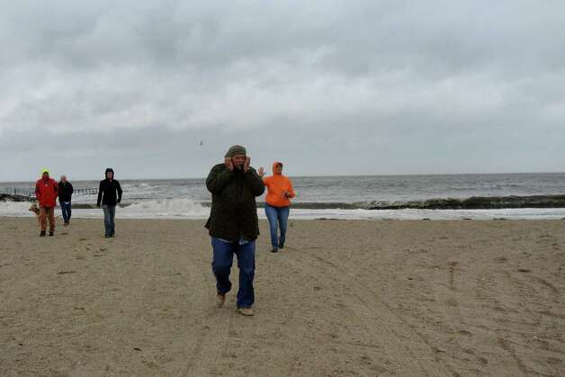 People brave the elements to watch the waves pound the South Benson Marina beach area in Fairfield, Conn. on Monday, Oct. 29, 2012. High winds from Hurricane Sandy moved into southern Connecticut on Monday morning. Conditions are expected to get worse at the next high tide around midnight tonight. Photo: Cathy Zuraw