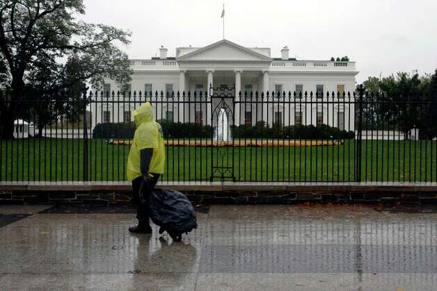 In this Monday, Oct. 29, 2012, photo, a lone man wearing a rain pouch walks past the White House in Washington, Monday, Oct. 29,2012, during the approach of Hurricane Sandy. Whoever wins the U.S. presidential election will likely struggle to manage the biggest economic threats he'll face. That's the cautionary message that emerges from the latest Associated Press Economy Survey. (AP Photo/Jacquelyn Martin) Photo: Jacquelyn Martin, Associated Press / AP