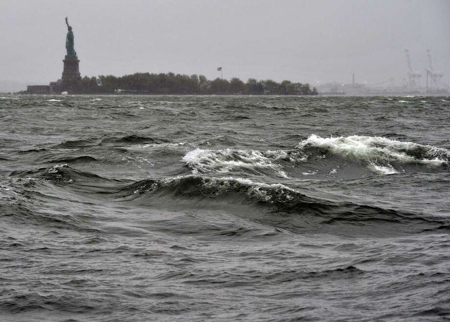 """High surf on the Hudson River near the Statue of Liberty  October 29, 2012 as New Yorkers prepare for Hurricane Sandy expected to hit the city later tonight Much of the eastern United States was in lockdown mode October 29, 2012 awaiting the arrival of a hurricane dubbed """"Frankenstorm"""" that threatened to wreak havoc on the area with storm surges, driving rain and devastating winds.  AFP PHOTO / TIMOTHY A. CLARYTIMOTHY A. CLARY/AFP/Getty Images Photo: TIMOTHY A. CLARY, AFP/Getty Images / AFP"""