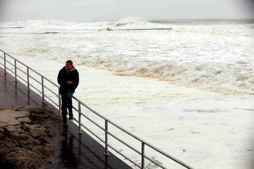 A man sits on a railing at Rockaway Beach Boulevard ahead of Hurricane Sandy on October 29, 2012 in the Queens borough of New York City. The storm, which threatens 50 million people in the eastern third of the U.S., is expected to bring days of rain, high winds and possibly heavy snow. New York Governor Andrew Cuomo announced the closure of all New York City's bus, subway and commuter rail service as of Sunday evening. Photo: Allison Joyce, Getty Images / 2012 Getty Images