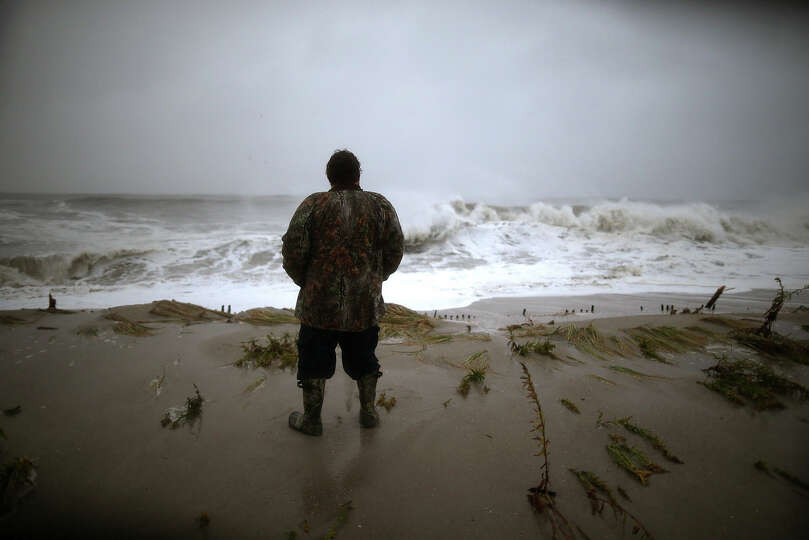 Andy Becica stands on the beach watching the heavy surf from Hurricane Sandy wash in in, on Octobe